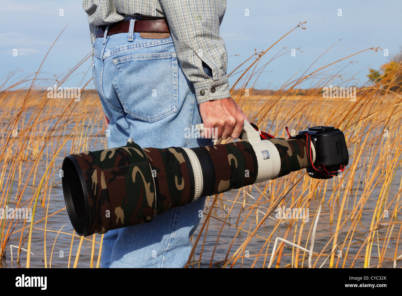 Professional photographer carrying a camouflaged Canon super telephoto lens and DSLR. - Stock Image
