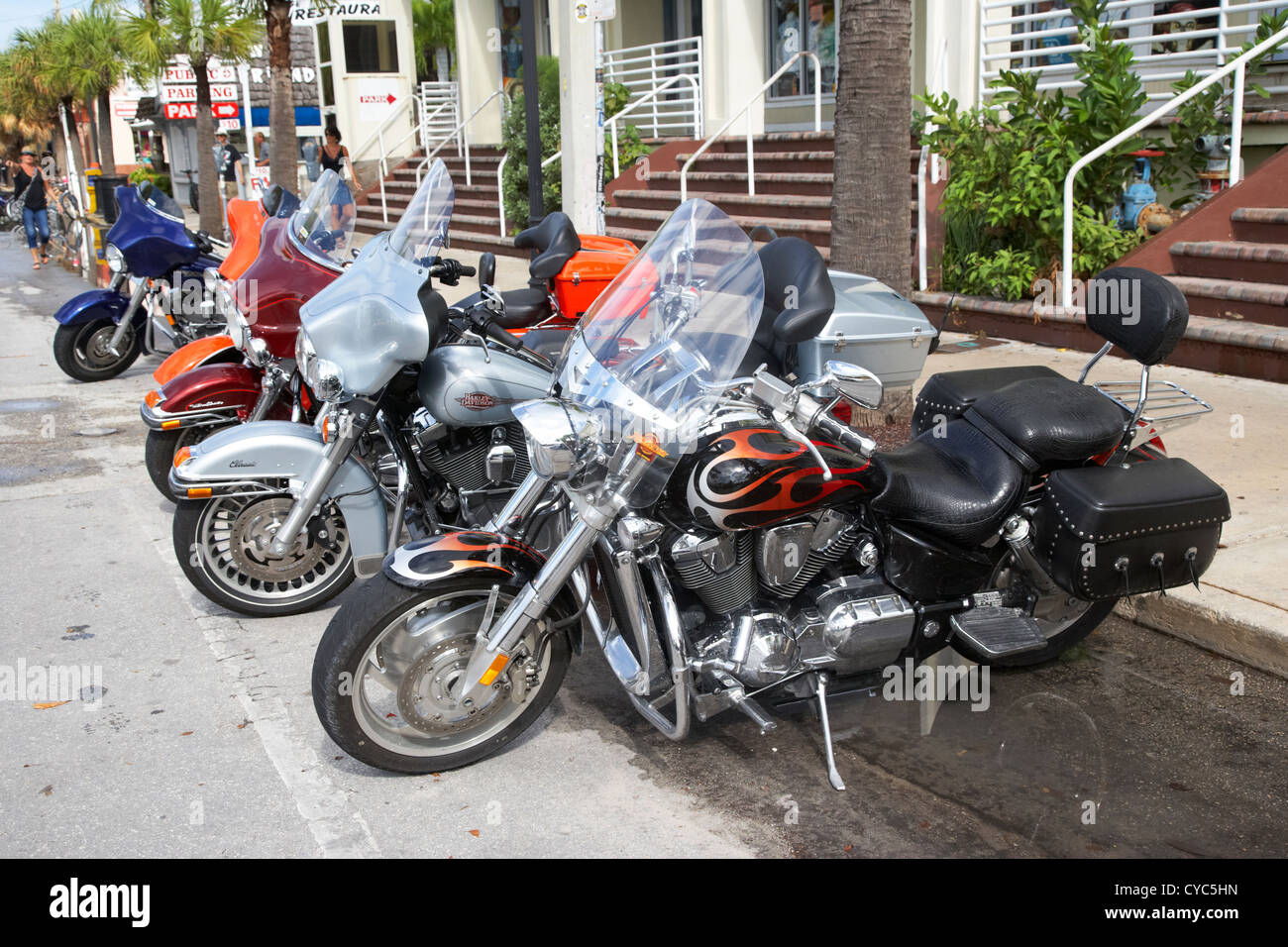 row of honda and harley davidson motorcycles parked in key west during bike week florida usa - Stock Image