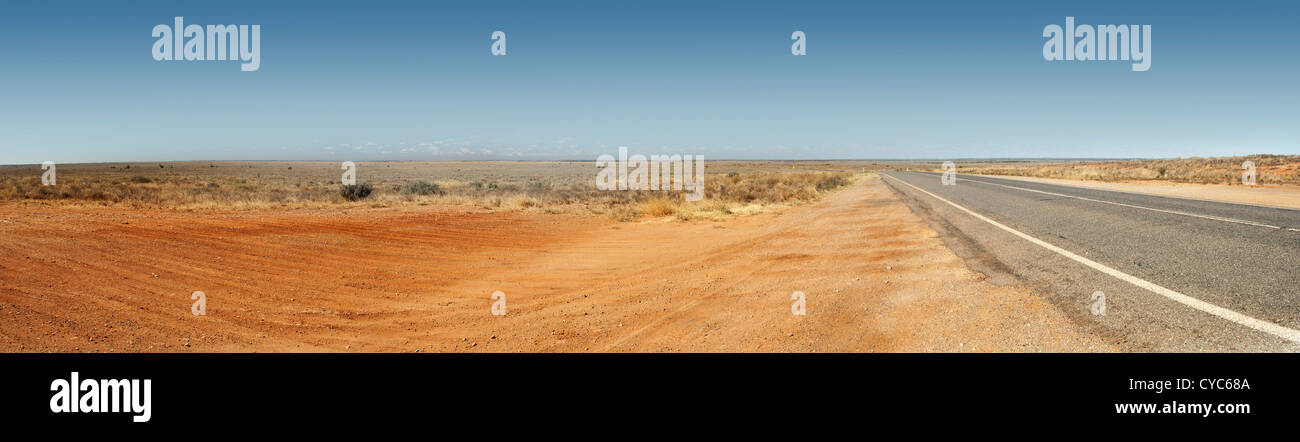 Panorama of the Australian Outback with red dirt and remote road - Stock Image