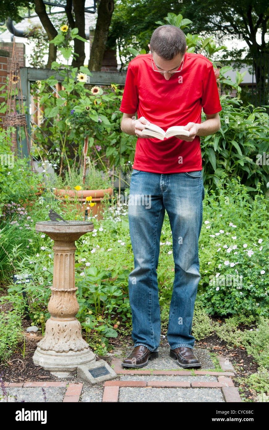 A man is standing up in a public garden reading a book - Stock Image