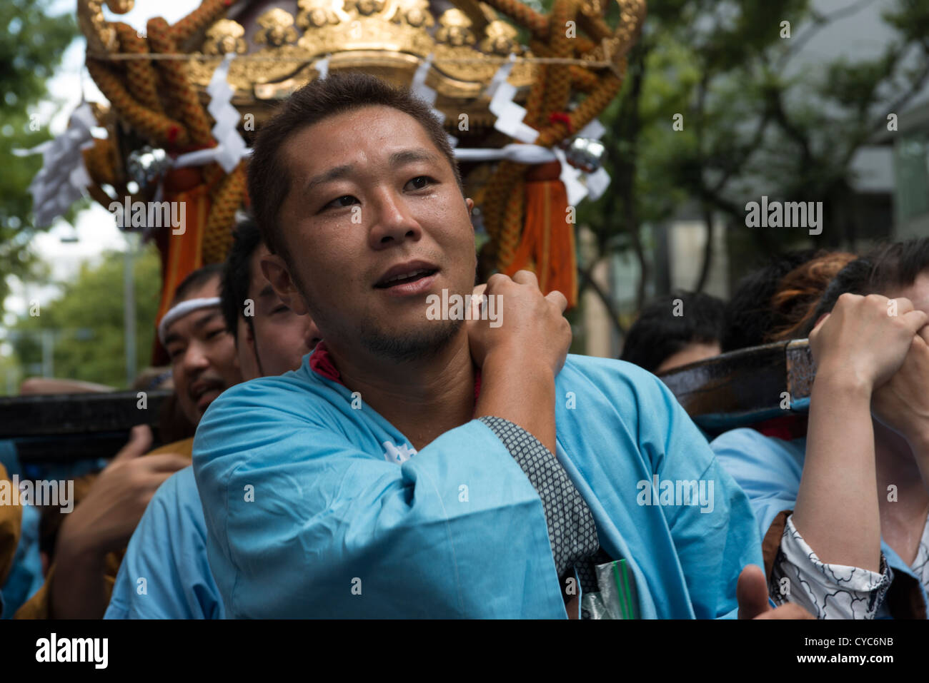 A crowd of worshippers carrying a portable mikoshi shrine Omote Sando Tokyo Japan - Stock Image