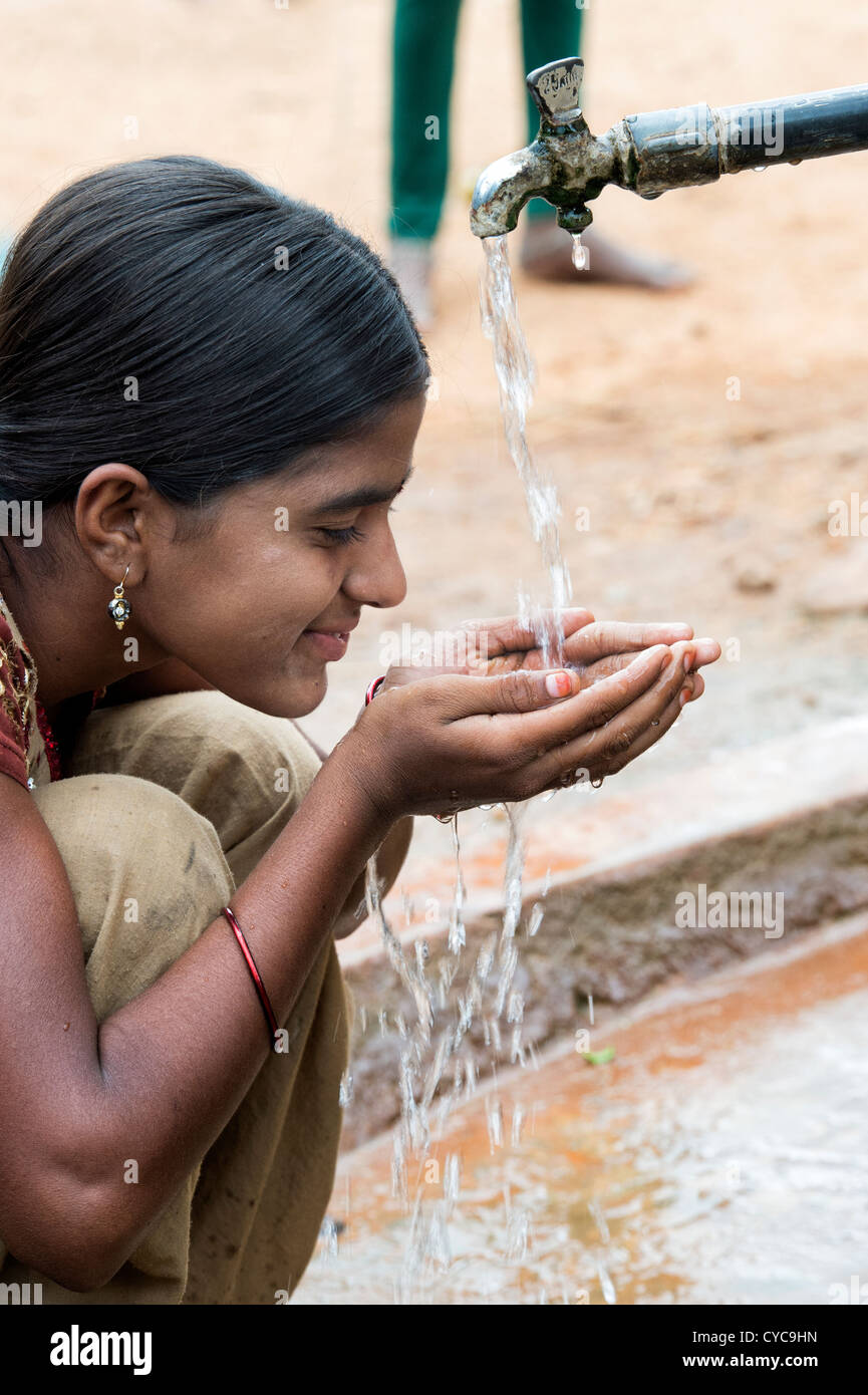 Indian girl drinking from a communal water tap in rural indian village. Andhra Pradesh, India - Stock Image