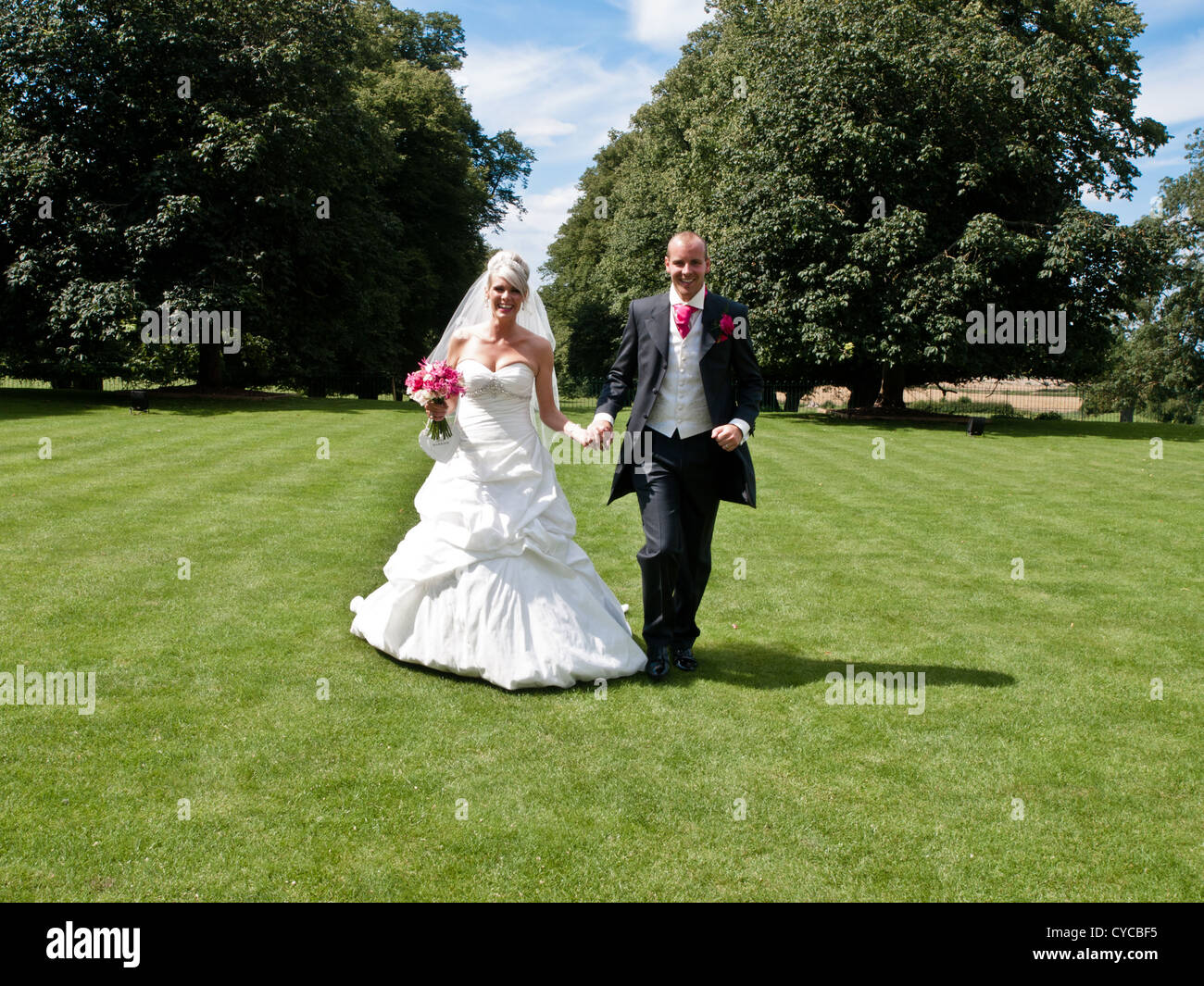 A newly wedded bride and groom stroll hand-in-hand through glorious green gardens on their wedding day - Stock Image
