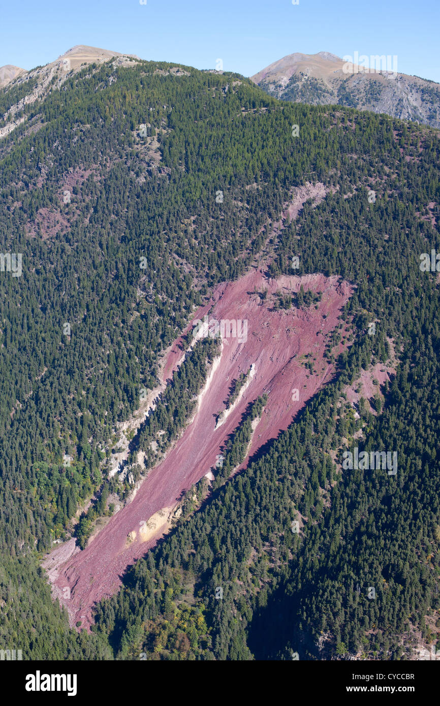 BLEEDING EARTH (aerial view). Landslide showing the red earth beneath the green canopy. Mercantour Alps, French - Stock Image