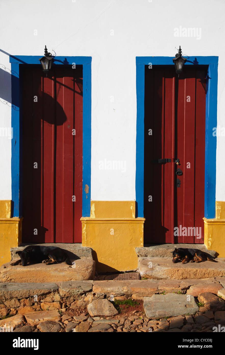 Dogs sleeping on steps of colourful doors of colonial building, Tiradentes, Minas Gerais, Brazil - Stock Image