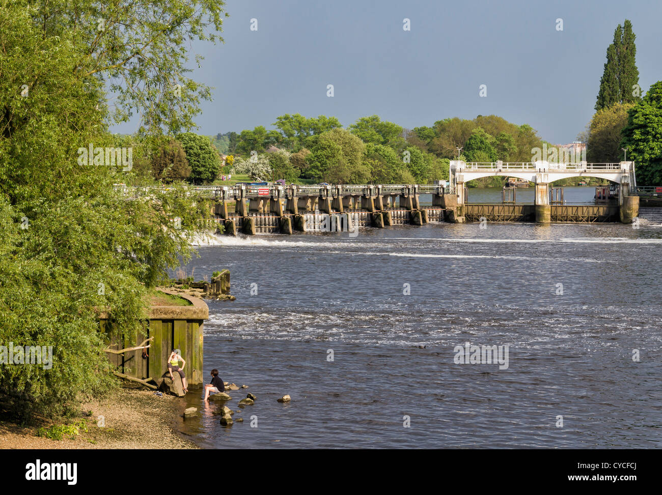 Two people sitting on the banks of the Thames river at Teddington Lock Stock Photo