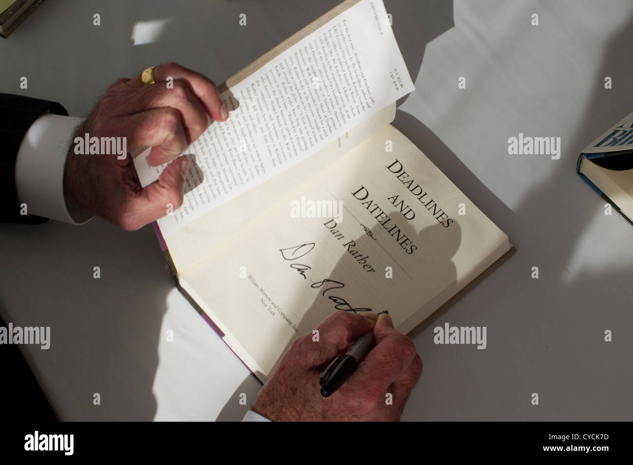 Journalist Dan Rather signs a copy of his book 'Deadlines and Datelines' for a fan at the Texas Book Festival - Stock Image