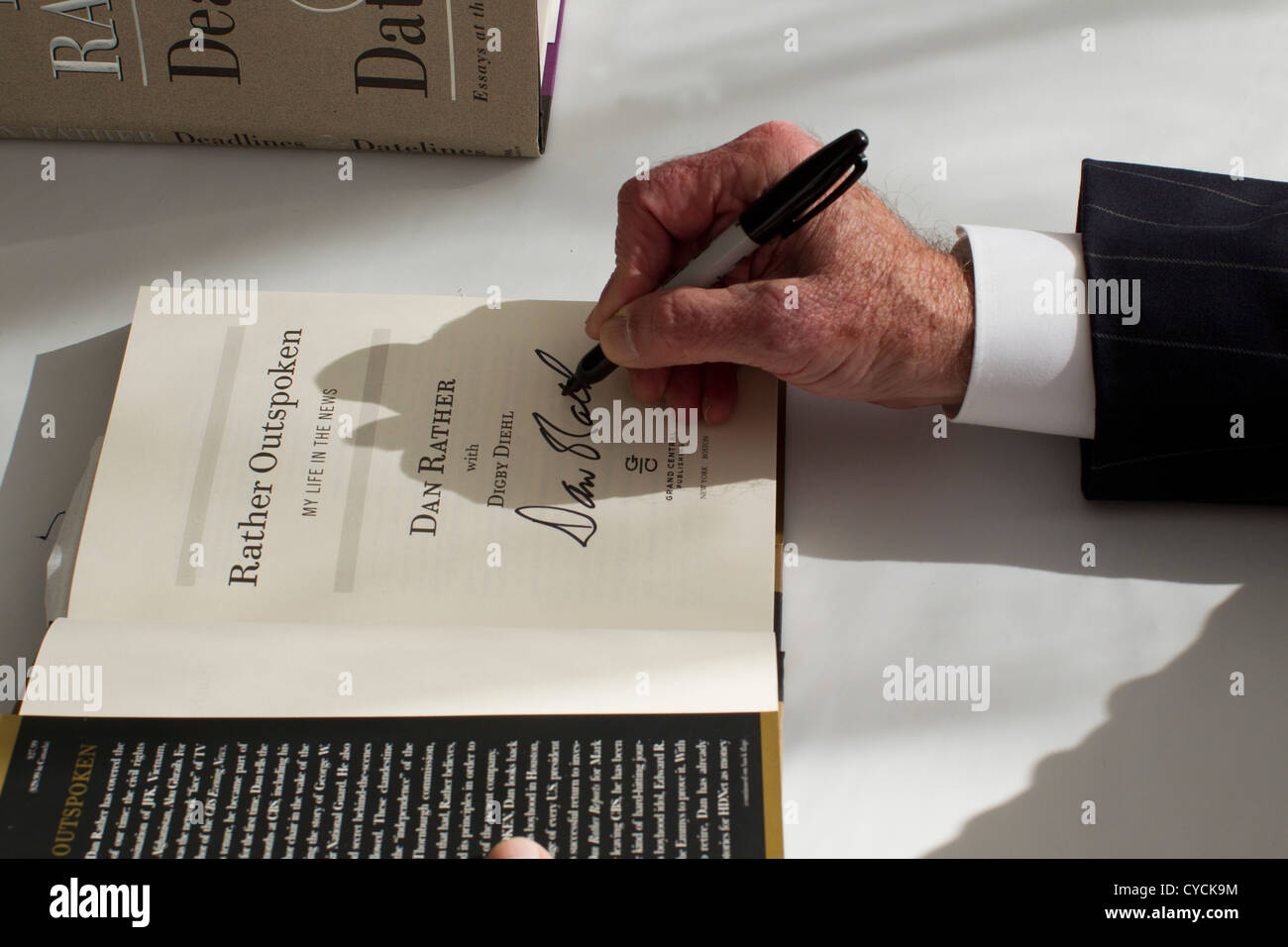 Journalist Dan Rather signs a copy of his book 'Rather Outspoken' for a fan at the Texas Book Festival in - Stock Image