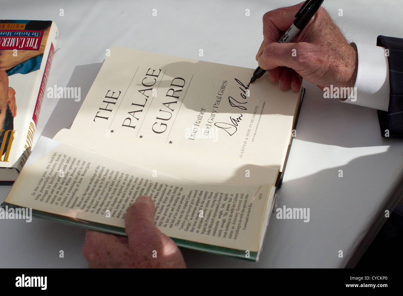 Journalist Dan Rather signs a copy of one of his earlier books, 'The Palace Guard,' for a fan at the Texas - Stock Image
