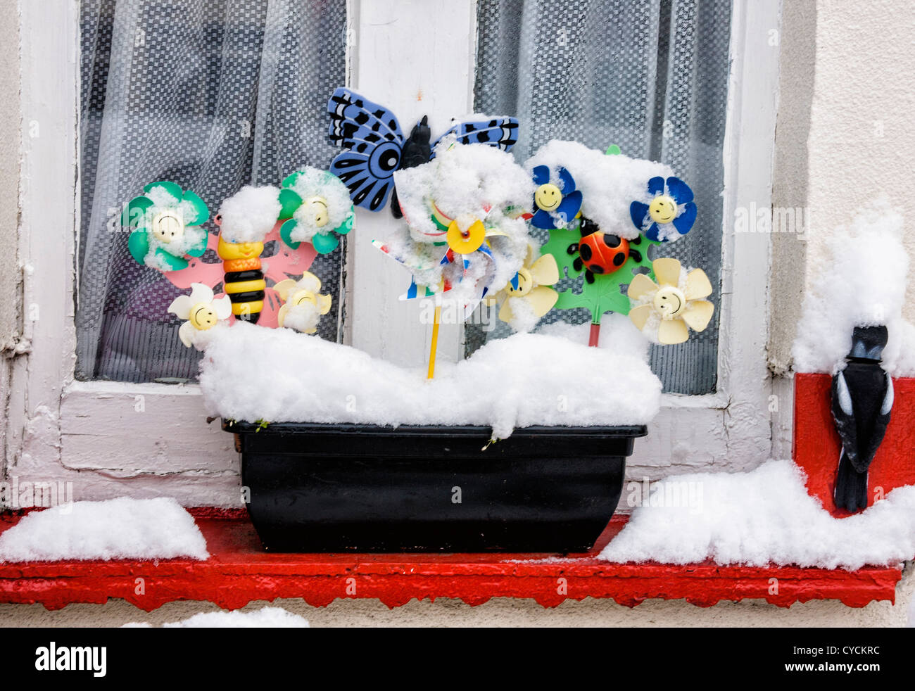 A quirky snow-covered window box - bees, butterflies and windmills - Stock Image