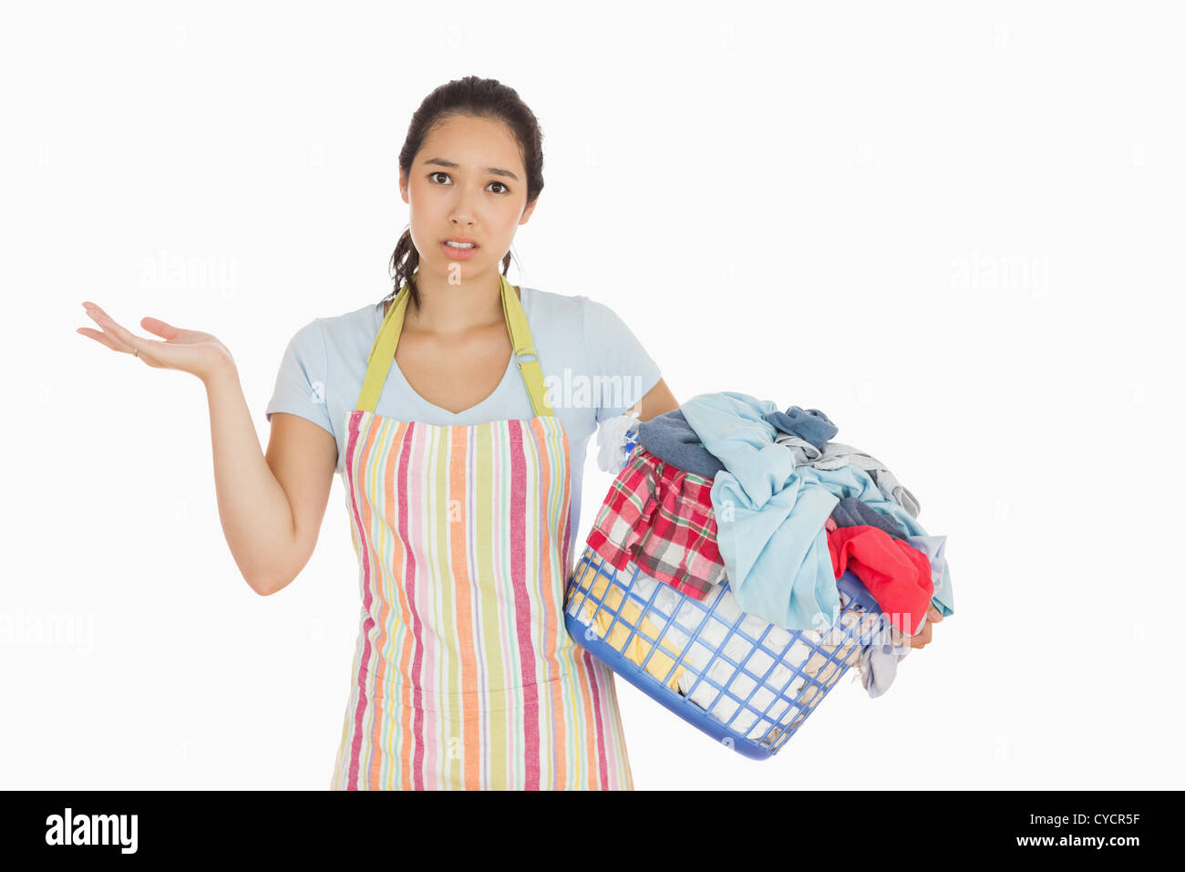 Puzzled young woman holding laundry basket full of dirty laundry - Stock Image