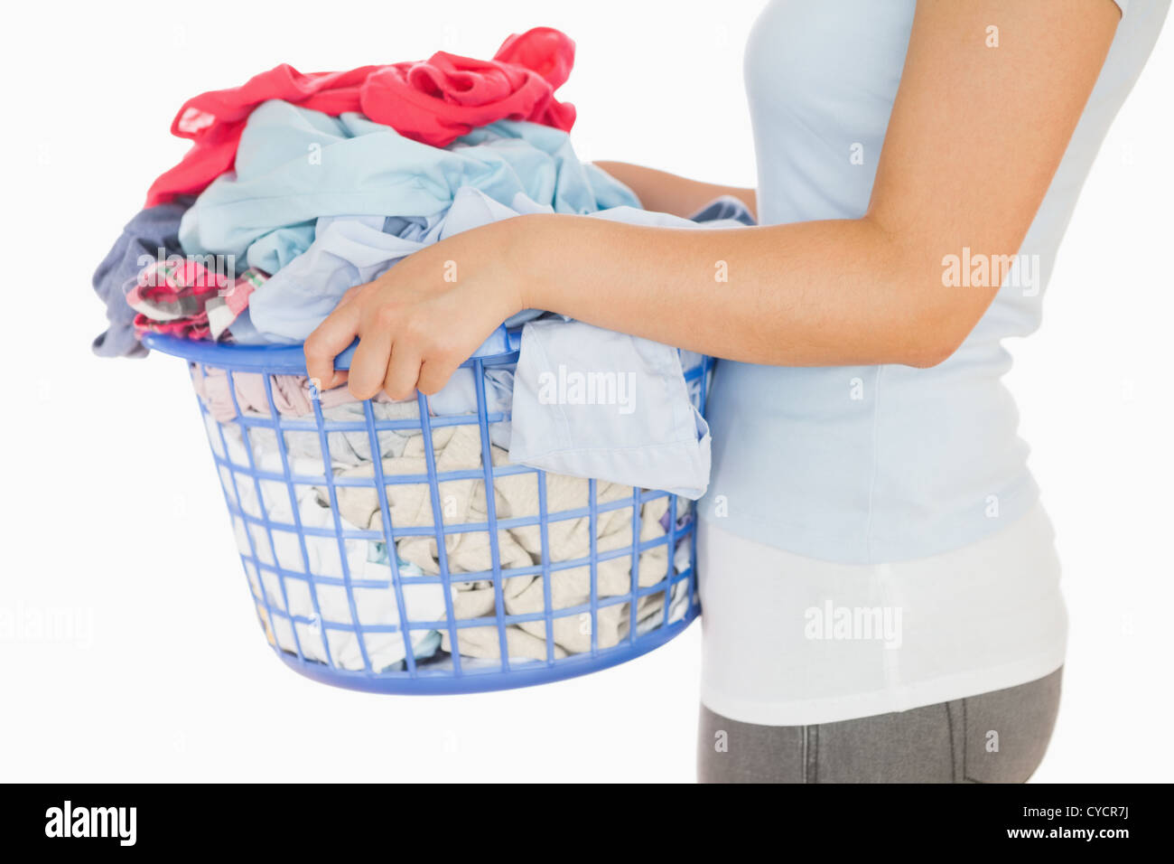 Woman holding a basket overflowing of laundry - Stock Image