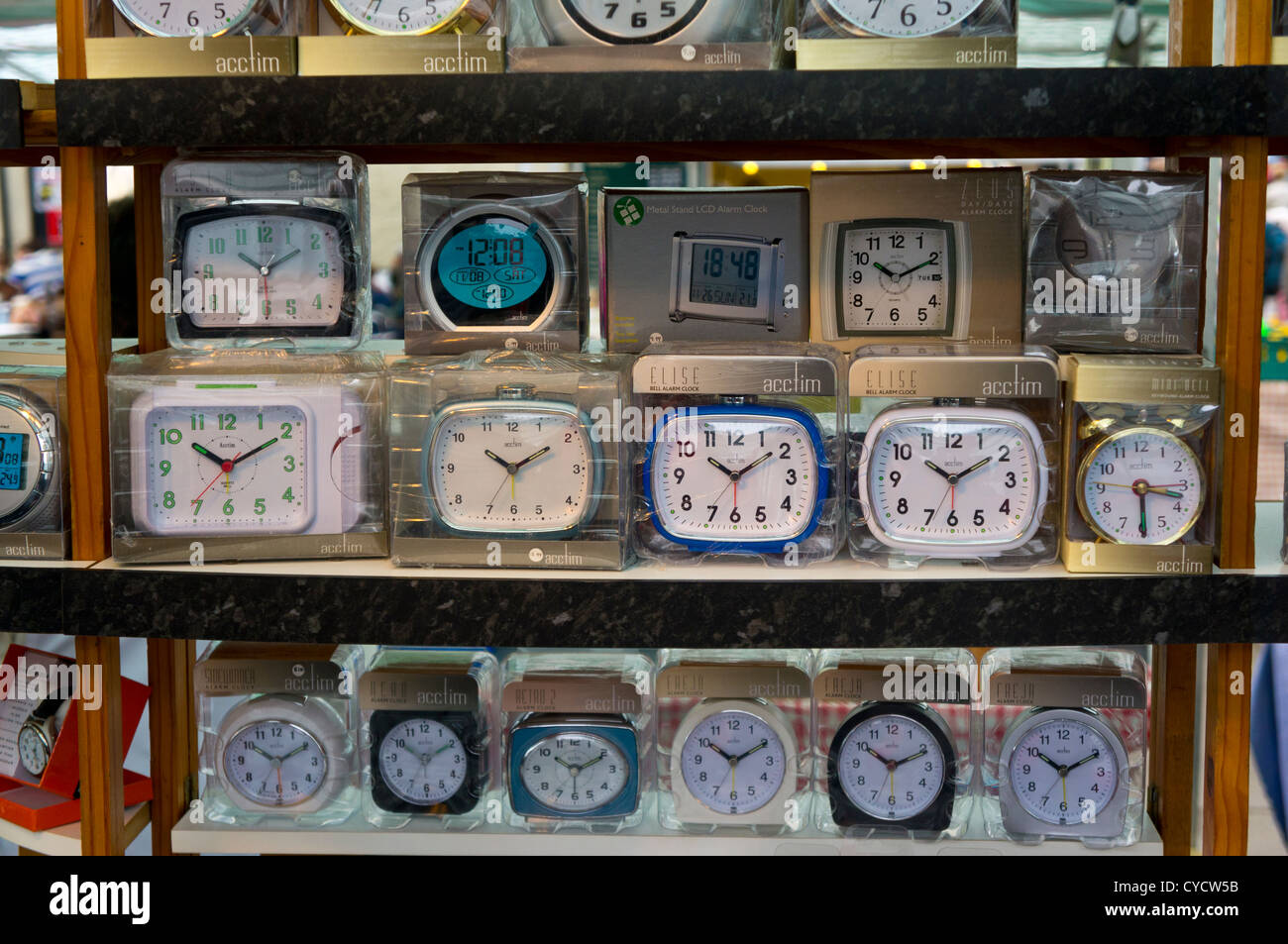 Rows of many different styles of alarm clock on a market stall - Stock Image