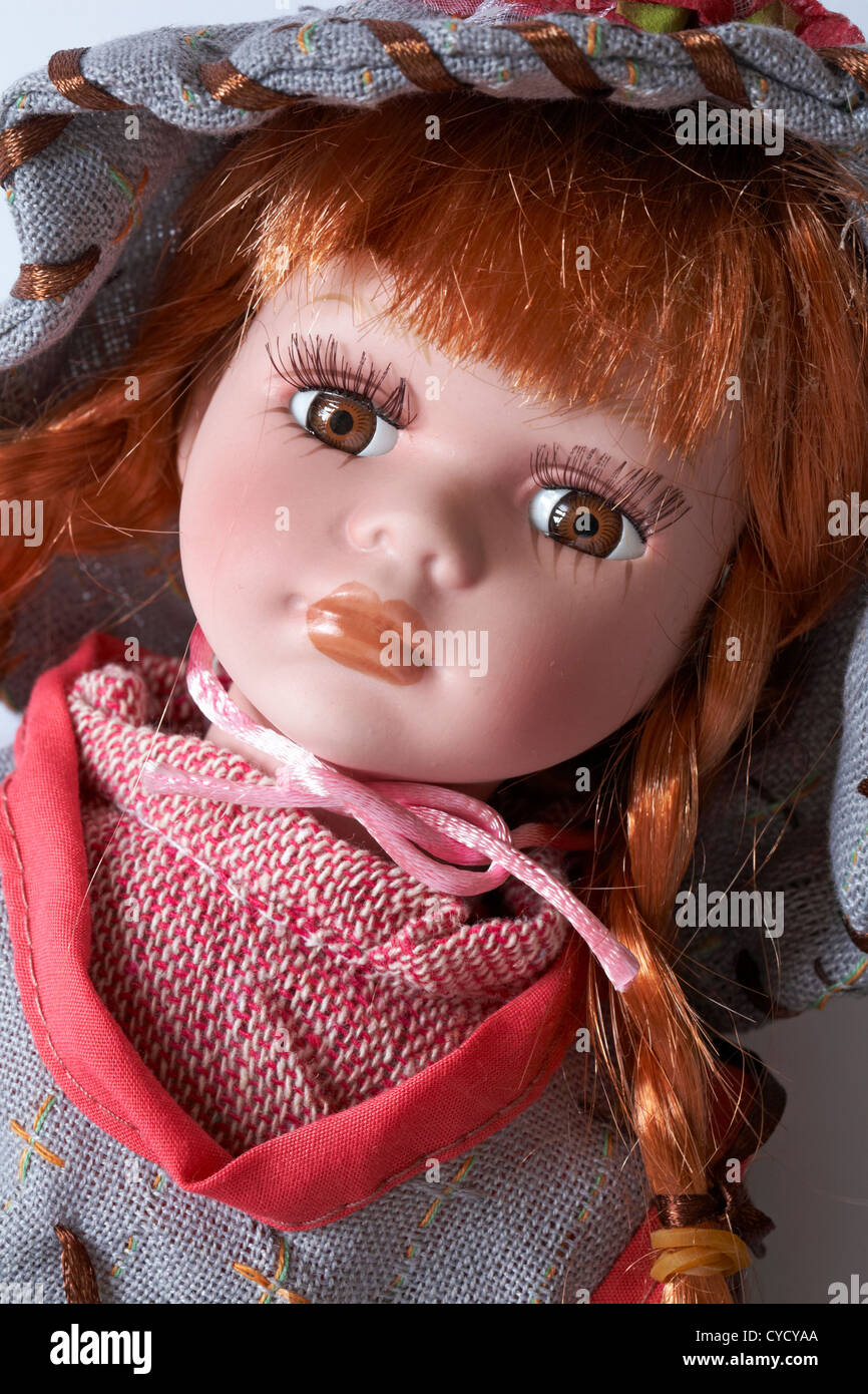 Close up of doll with long eyelashes and ginger red hair in plaits - Stock Image