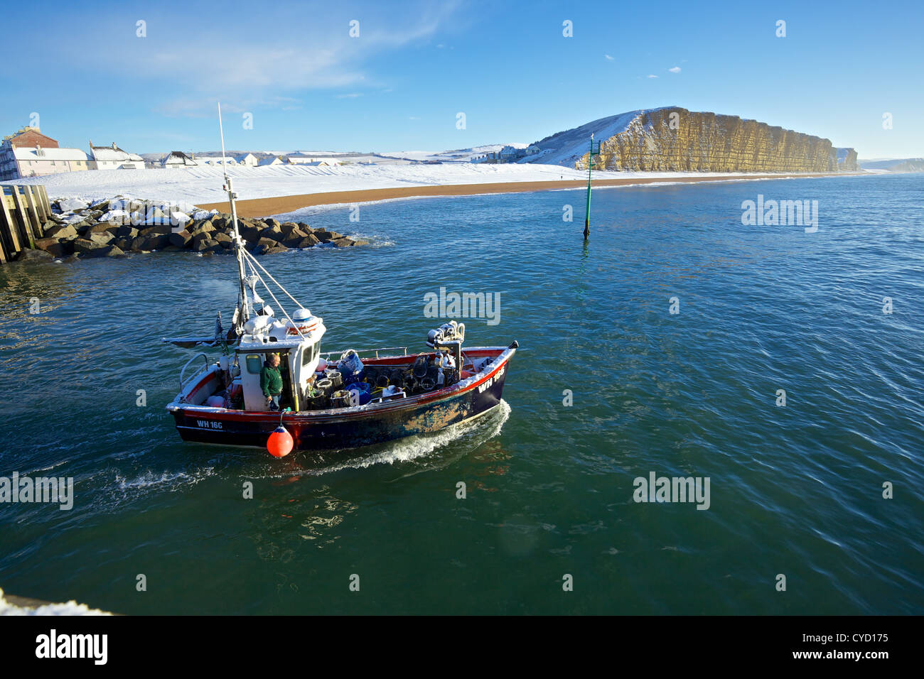 A fishing boat leaves West Bay Harbour, after snow covers the beach - Stock Image