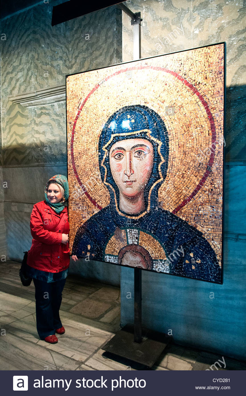 Woman tourist posing for a photograph with a photograph of the mosaic of the Virgin Mary, Aya Sofya Mednani, Istanbul, - Stock Image