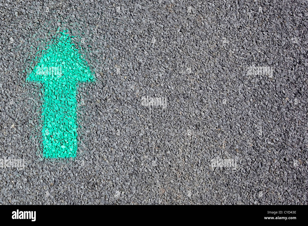 Background image of a green arrow spray painted onto a tarmac road surface - Stock Image