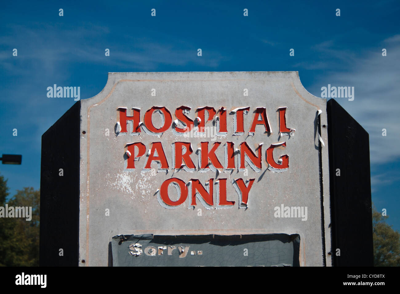 decrepit hospital parking only sign with peeling letters. - Stock Image