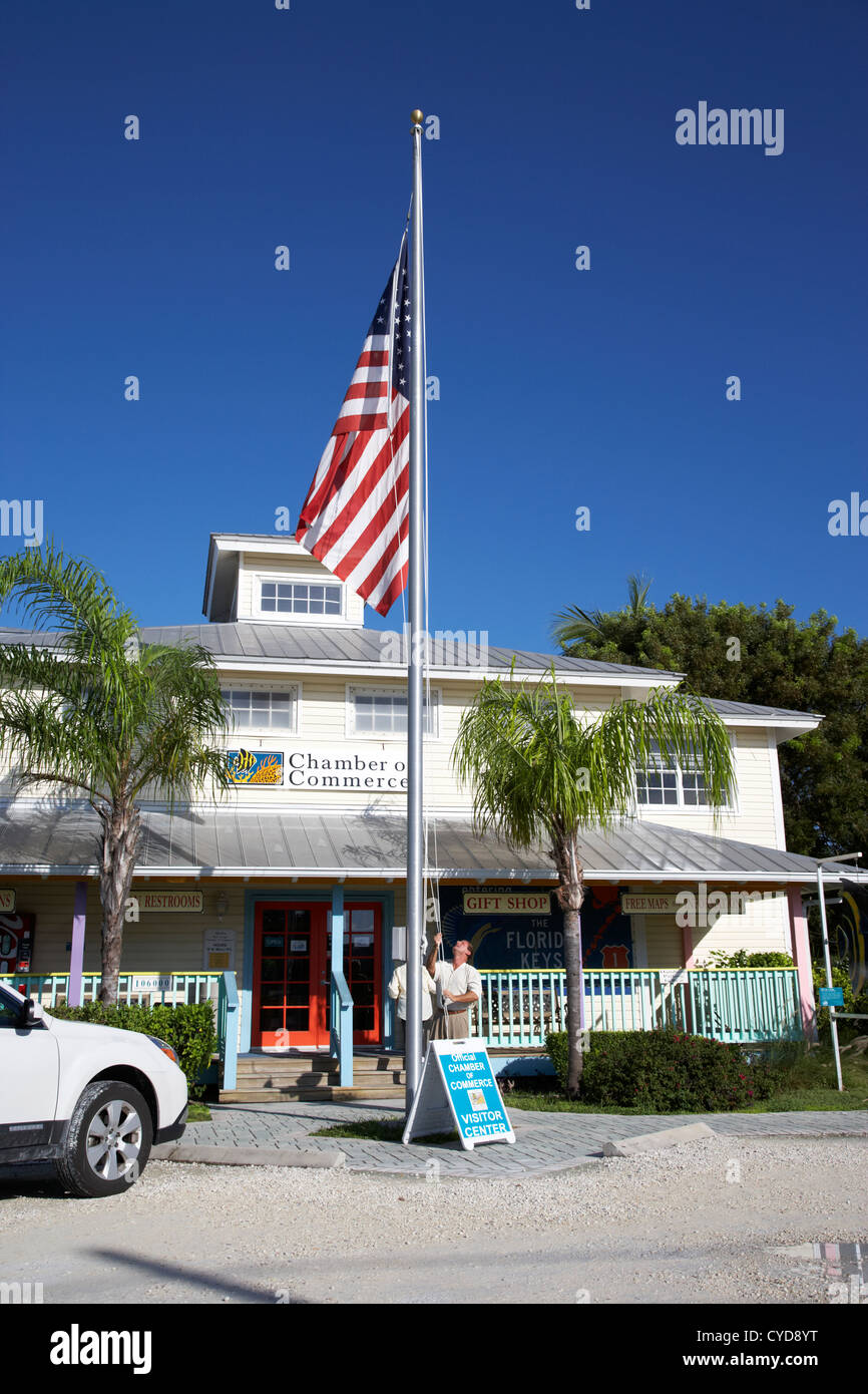 raising the american flag on a flagpole outside the chamber of commerce building in key largo florida keys usa Stock Photo