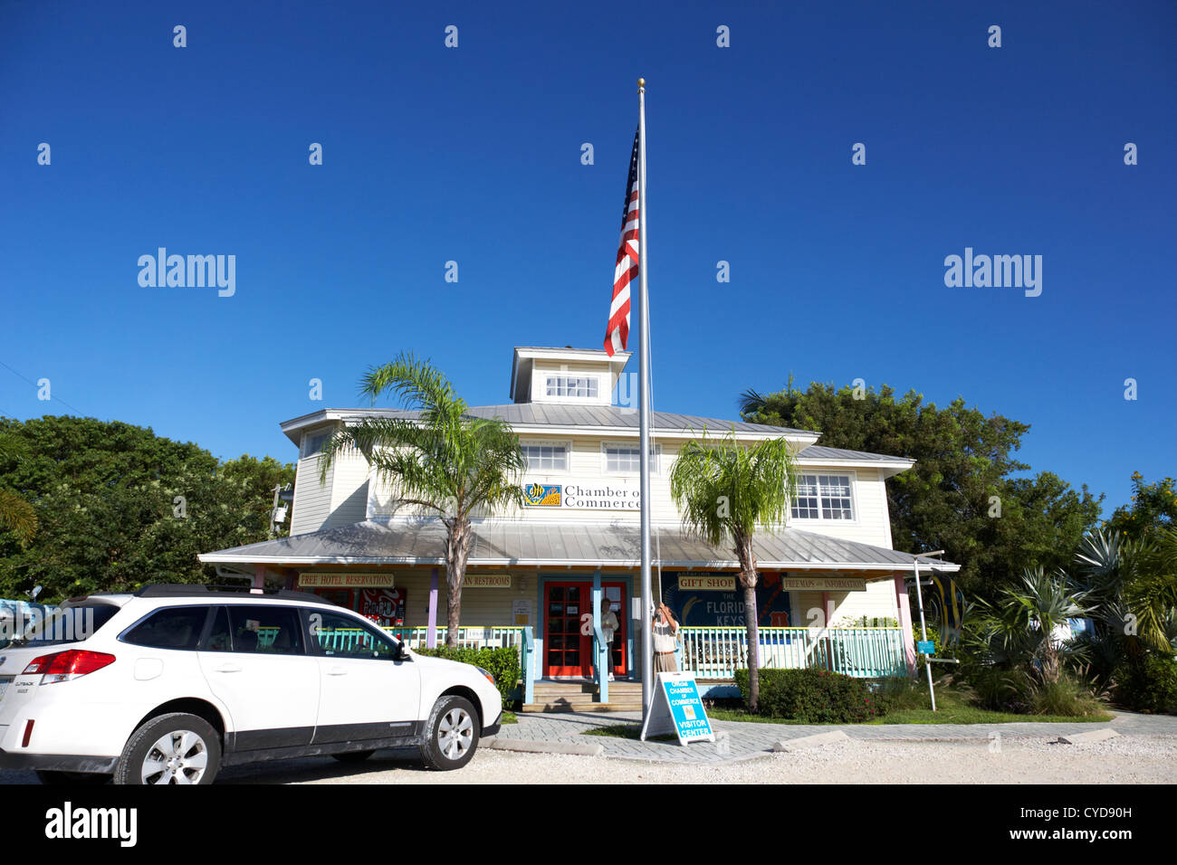 raising the american flag on a flagpole outside the chamber of commerce building in key largo florida keys usa - Stock Image