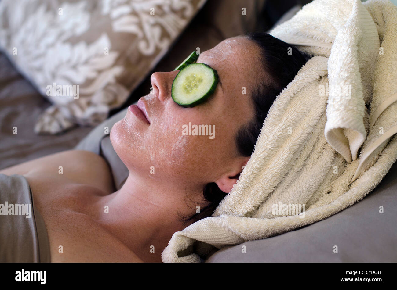 A young caucasian woman relaxes at home in bed with a natural eye and face treatment. - Stock Image