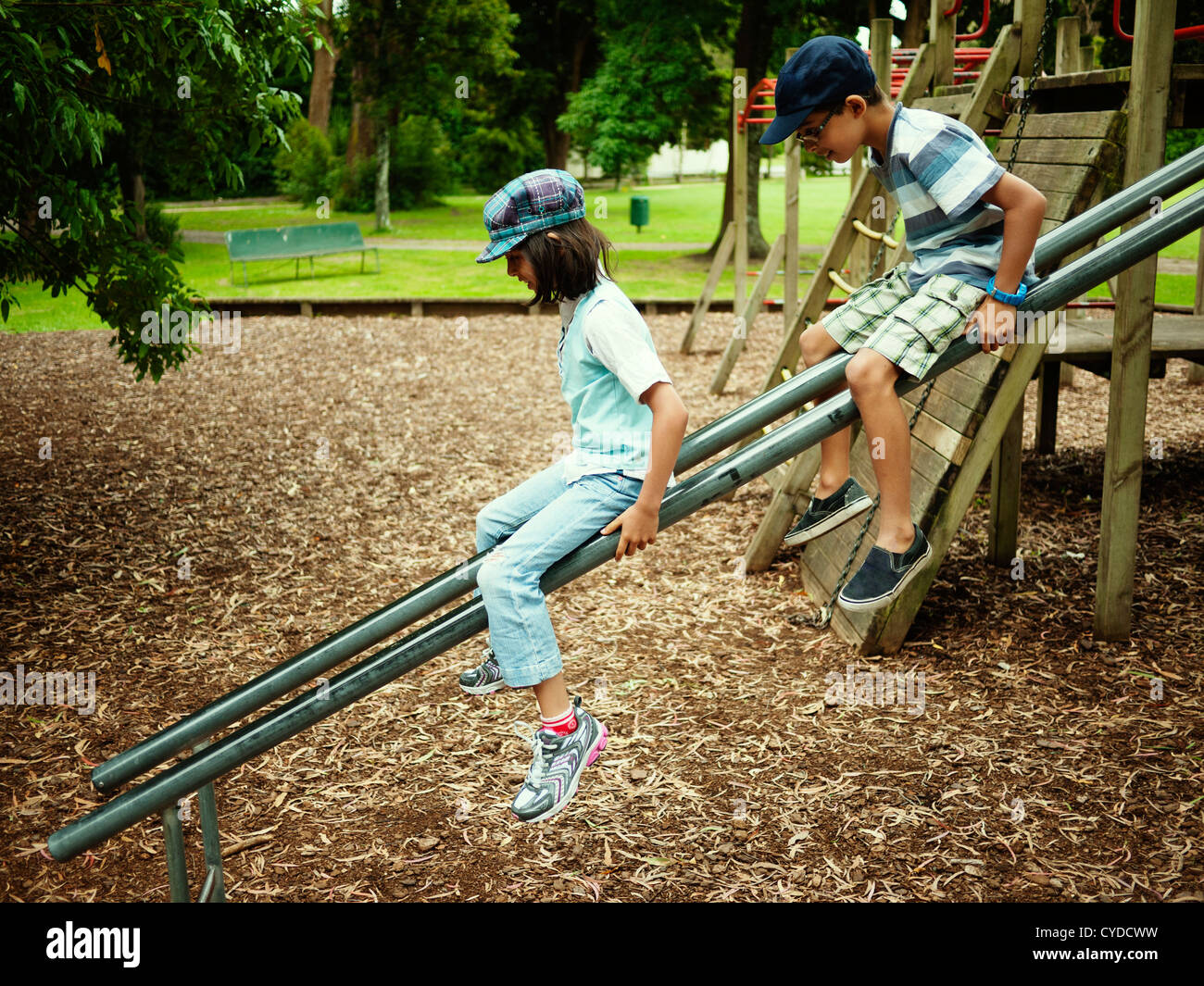Brother and sister on slide made of two scaffold bars, New Zealand. - Stock Image