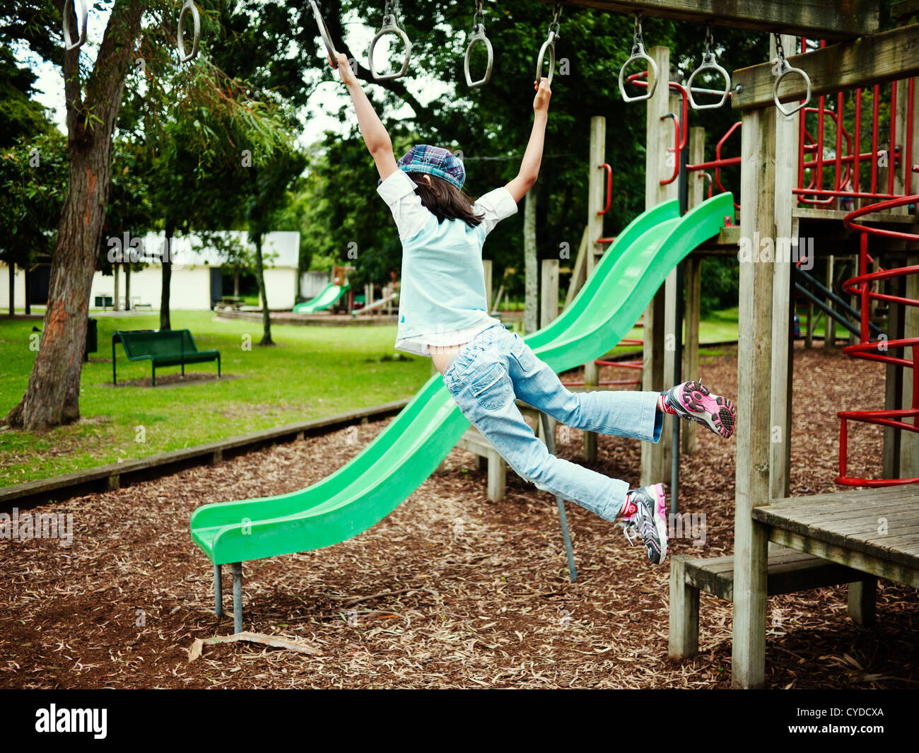 Children swing on monkey bars in adventure playground, New Zealand. - Stock Image