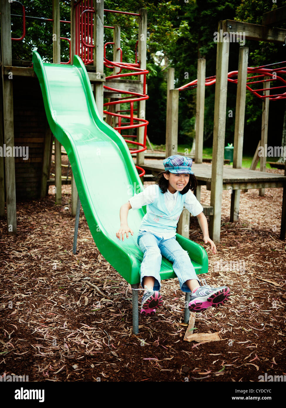 Girl shoots off end of slide. - Stock Image