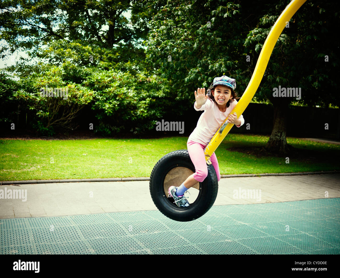 Girl waves as she rides roundabout at park. - Stock Image
