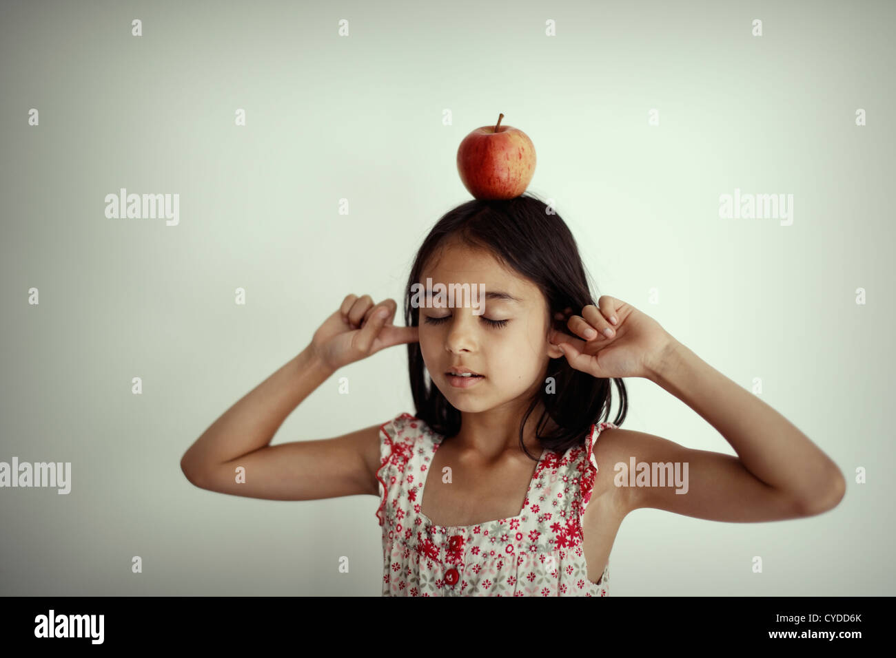 Girl balances apple on head with eyes shut and fingers in ears. - Stock Image