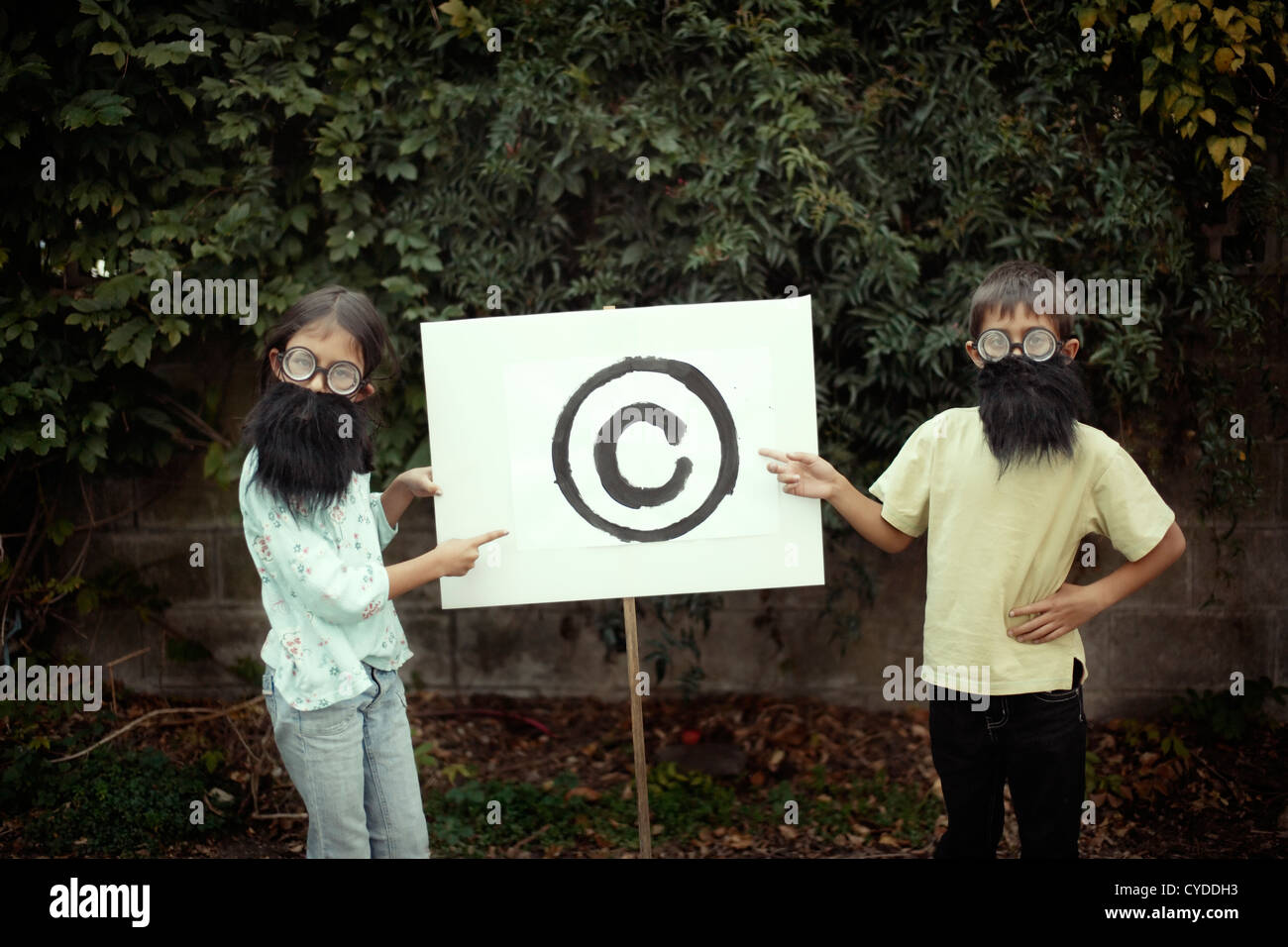 Boy and girl dressed up with fake beards point to copyright symbol. - Stock Image