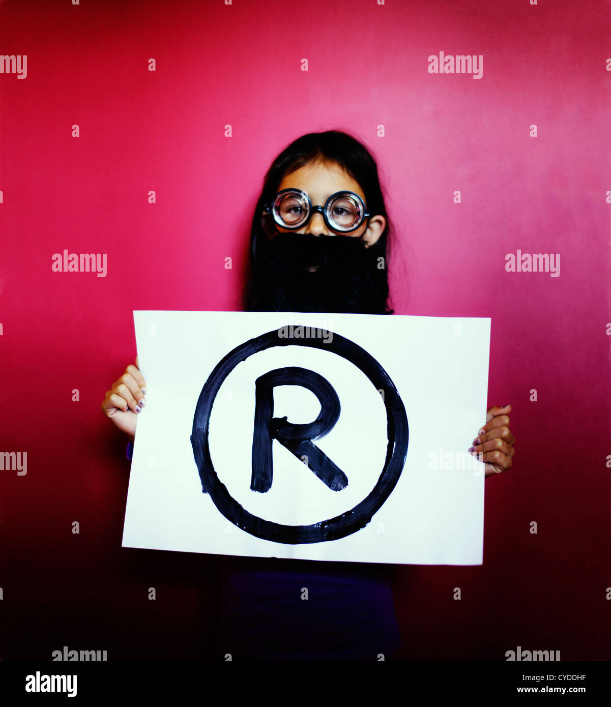 The professor says, 'Hands off: it's a Registered trademark'. Girl with fake beard and glasses holds - Stock Image