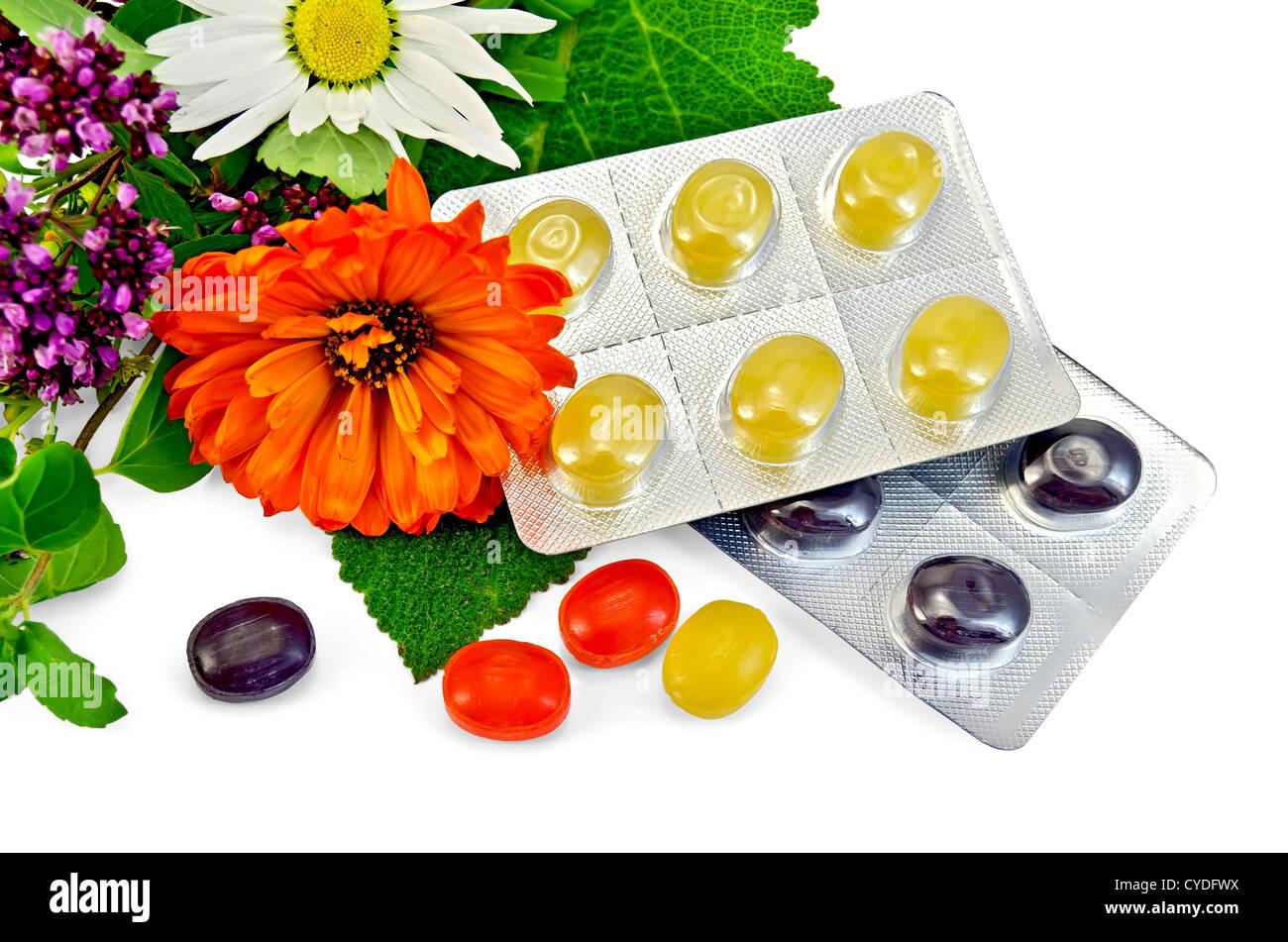 Lozenges cough multicolored, sprig of mint, sage leaf, chamomile, calendula, oregano isolated on white background - Stock Image