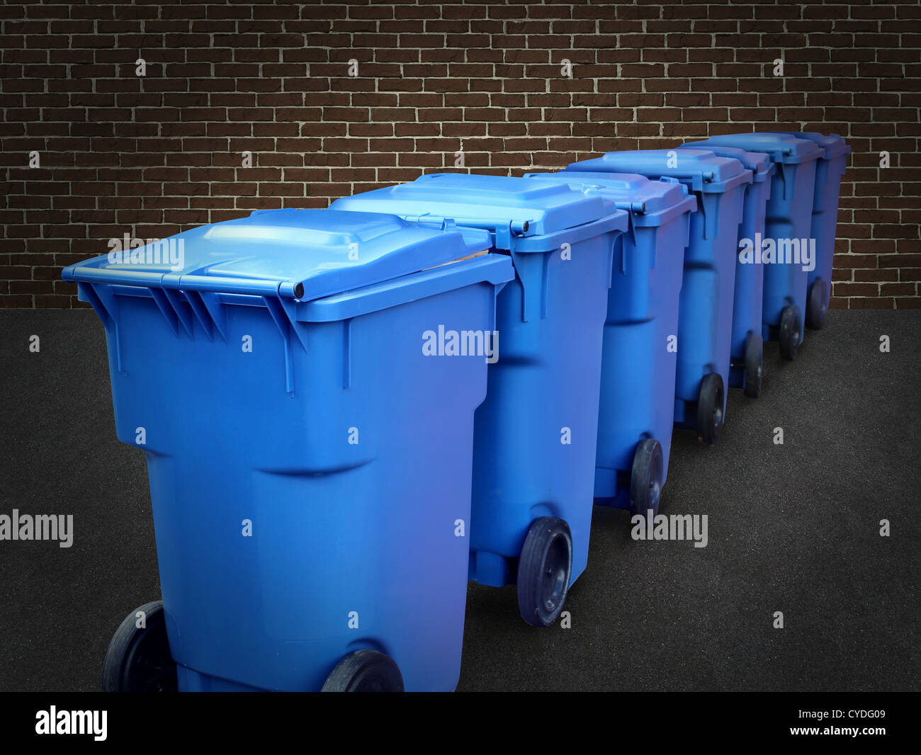 Recycle bins in a group made of commercial size blue plastic containers in a city street back alley against a brick Stock Photo