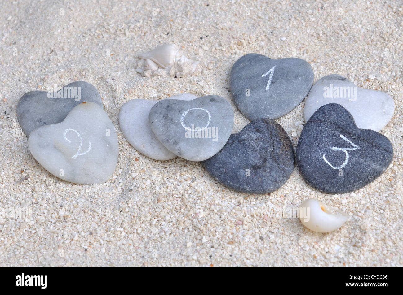 four stone hearts with 2013 inscription on the sand - Stock Image
