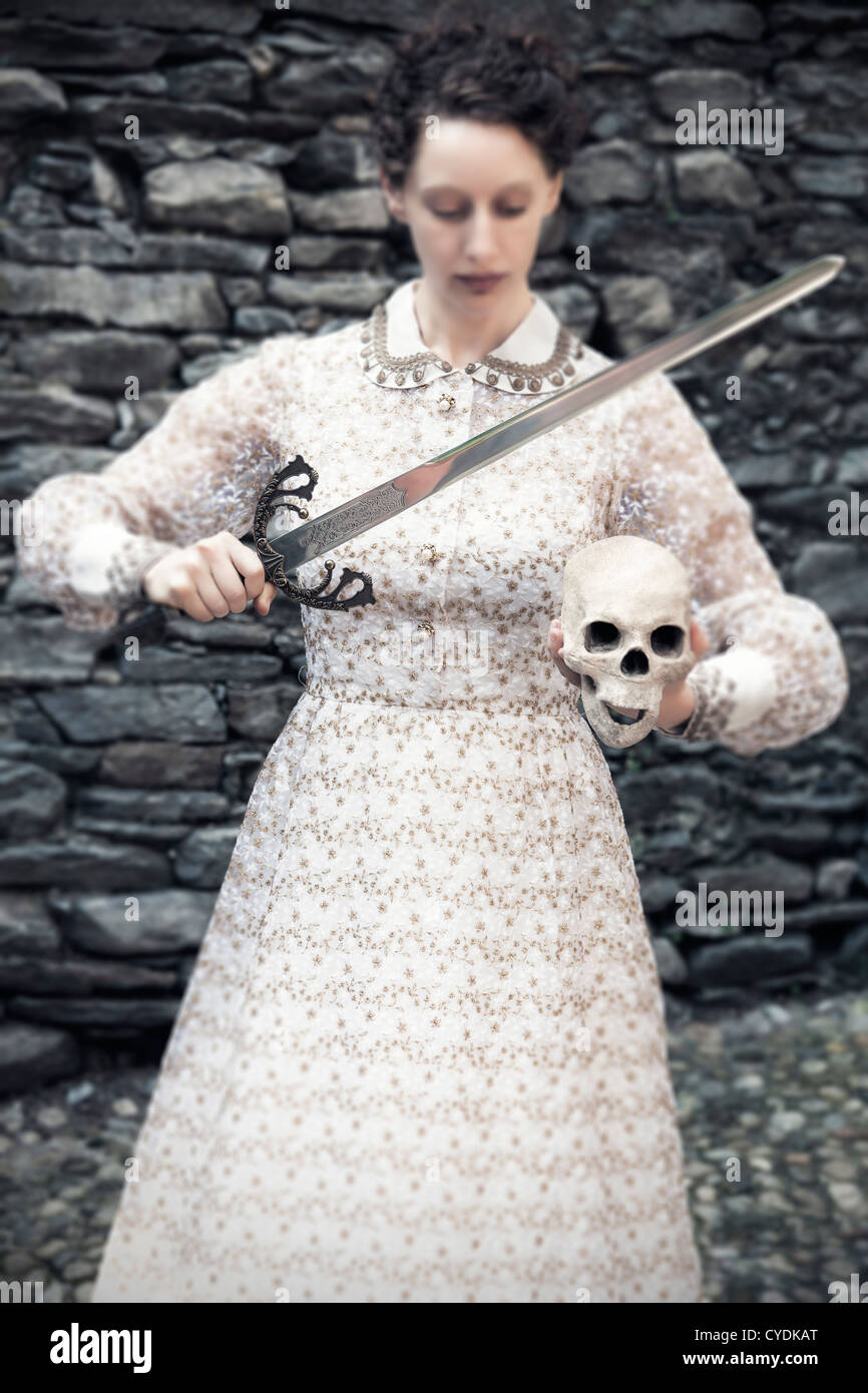 a woman in a victorian dress with sword and skull - Stock Image