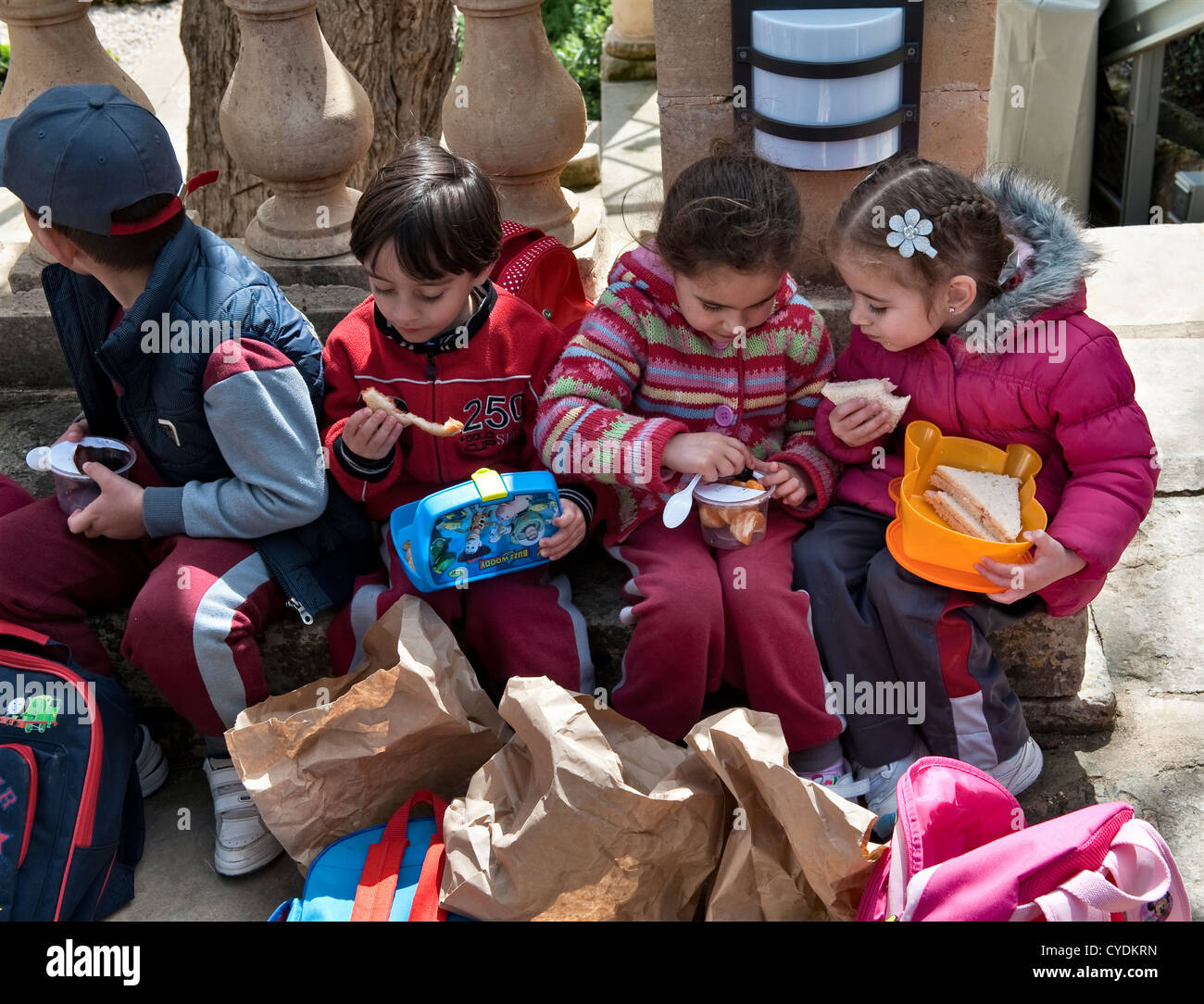 Malta. Small children eating their packed lunches while on a school trip to the President's Kitchen Garden - Stock Image