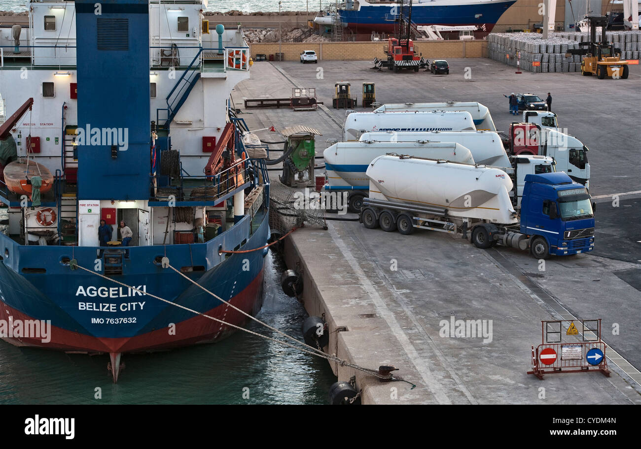 The port of Pozzallo, Sicily, Italy. The Belize-registered cargo ship Aggeliki taking on or discharging bulk cargo - Stock Image