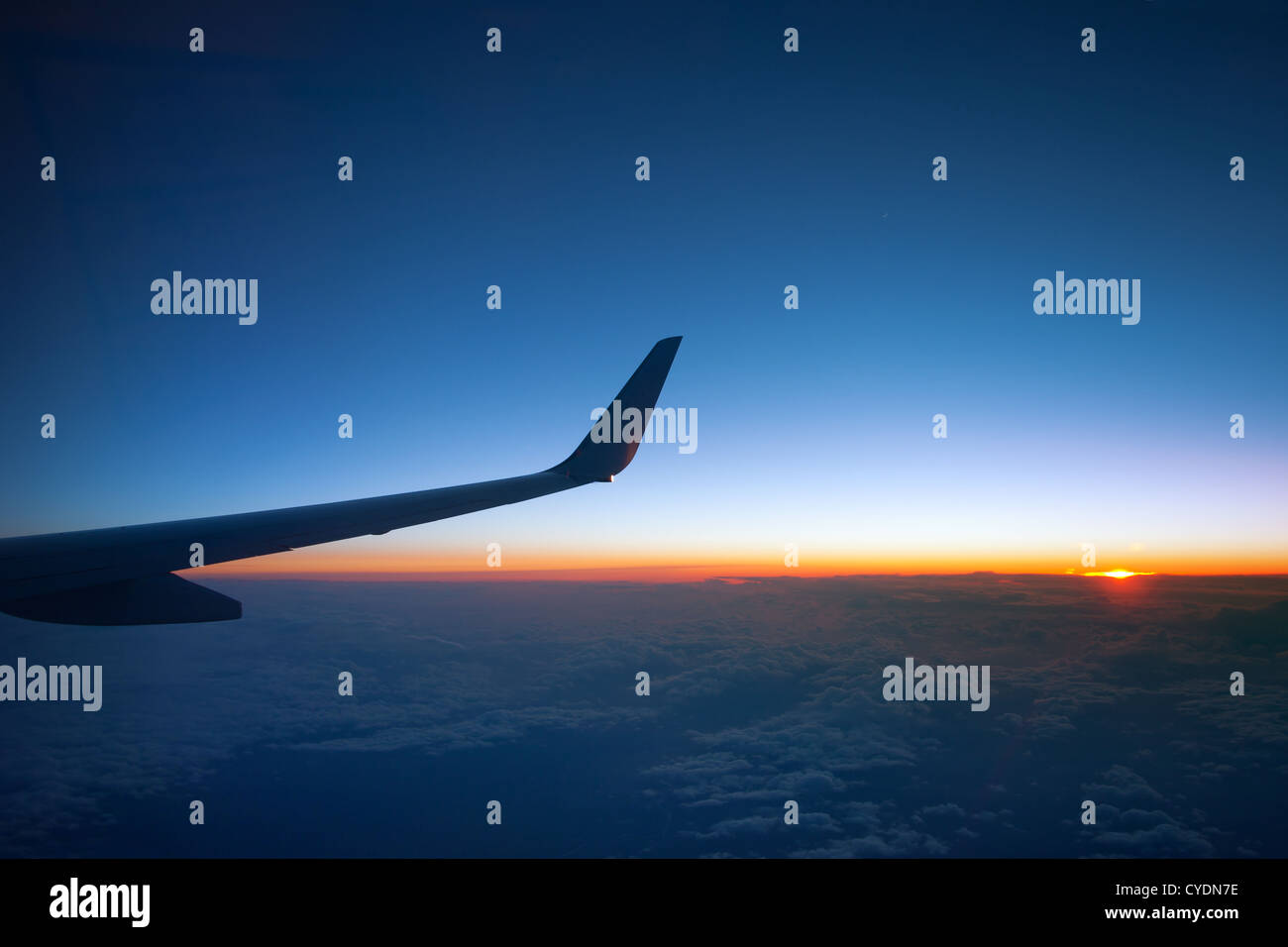 Above the clouds - sunset with airplane wing - Stock Image