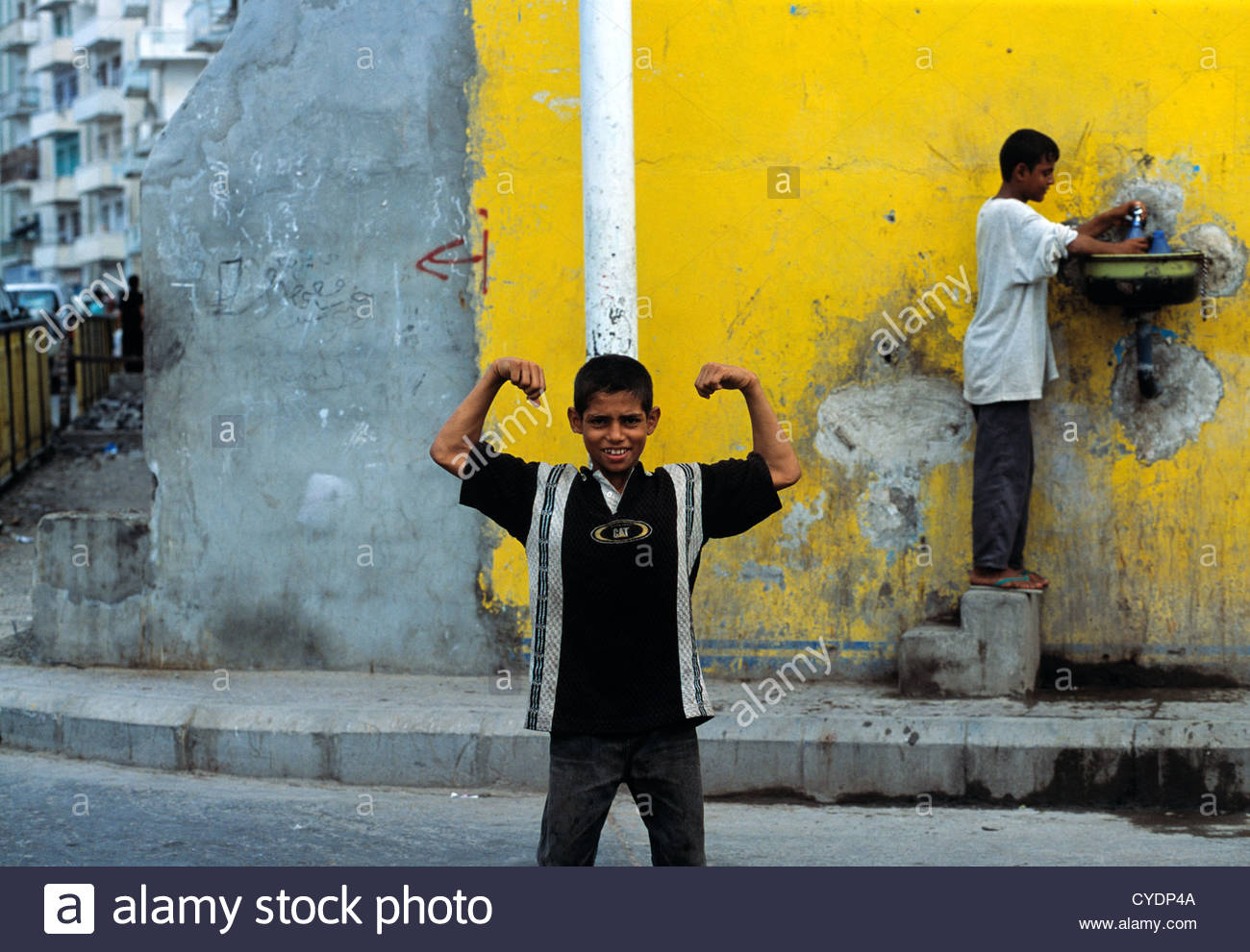 A young boy flexes his muscles in the port city of Aden in Yemen. - Stock Image