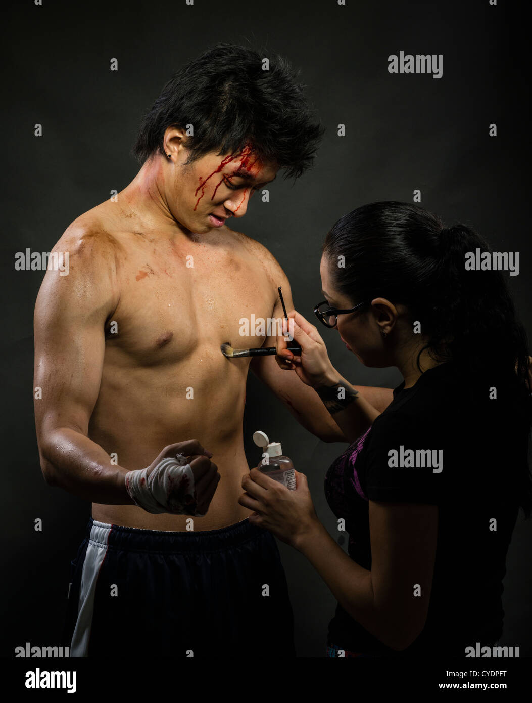 Makeup / special effects artist applies dirt and blood to the body of a model / actor - Stock Image