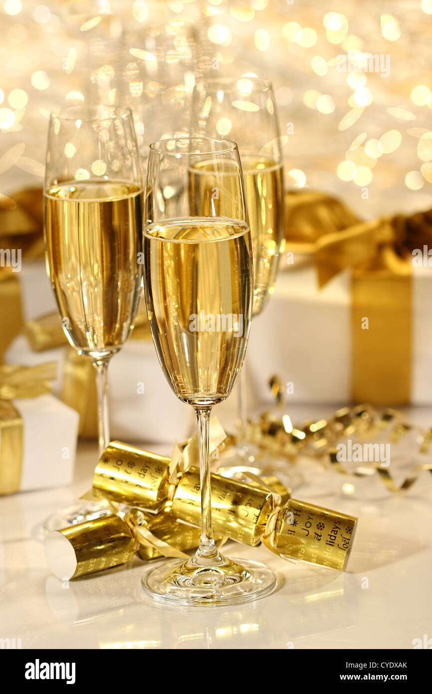 Glass of champagne against gold sparkle background - Stock Image