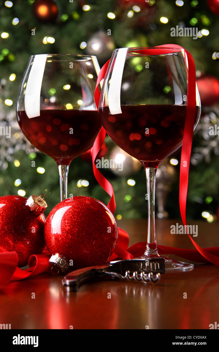 Holiday background with glasses of red wine while trimming tree - Stock Image
