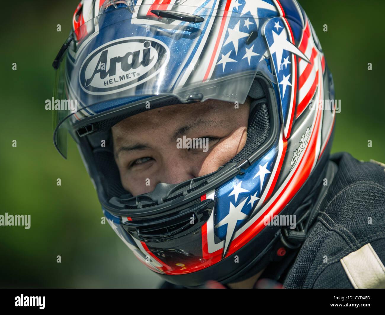 Motorbike rider wearing Arai helmet - Stock Image