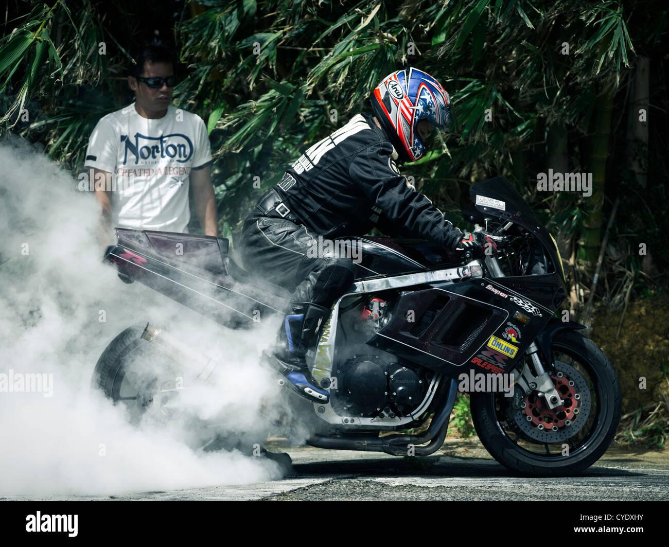 Motorbike smoking rear tire burnout. - Stock Image