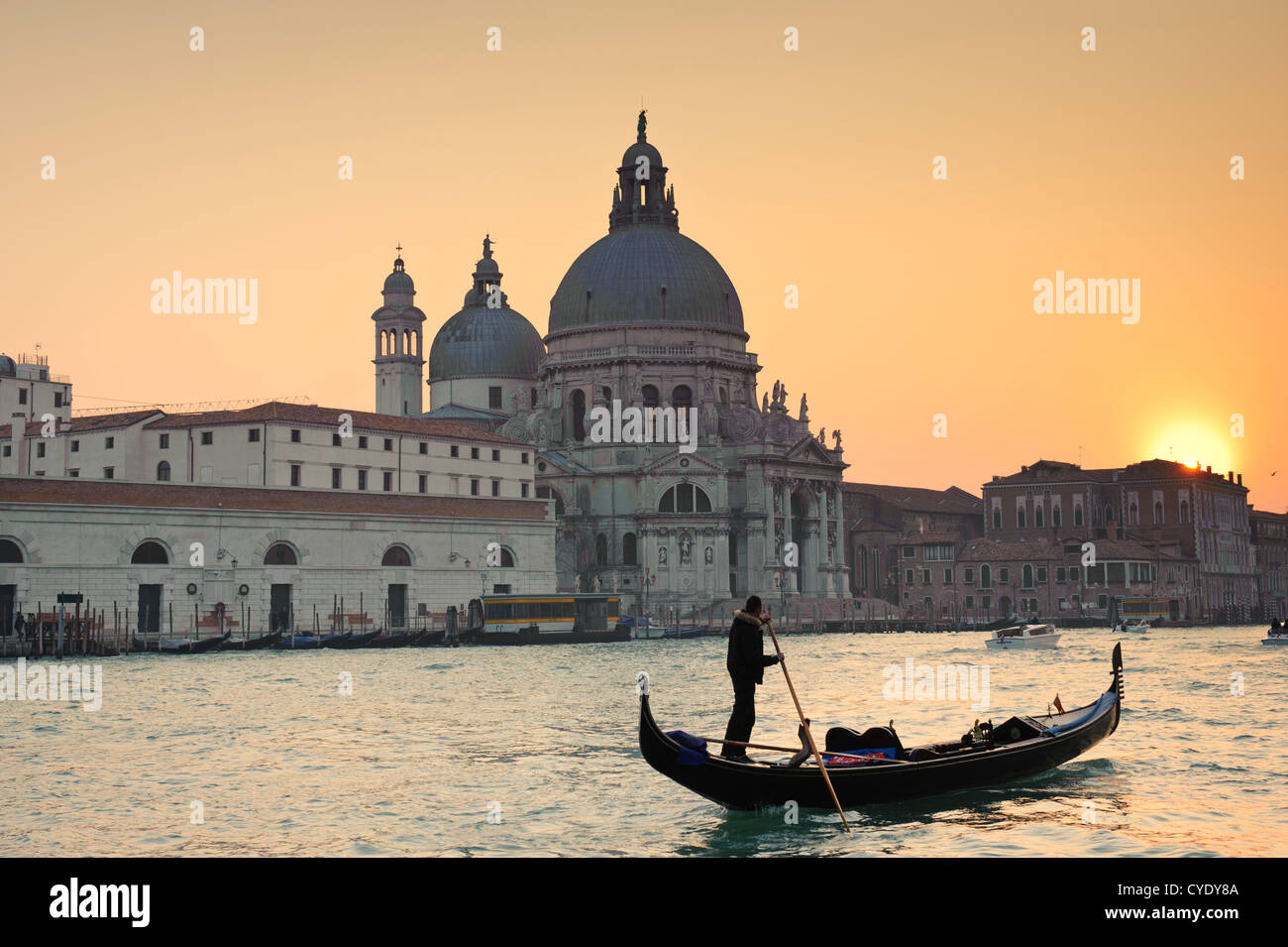 A Gondola in front of the Santa Maria della Salute Church at sunset time, Venice, Veneto, Italy. Stock Photo
