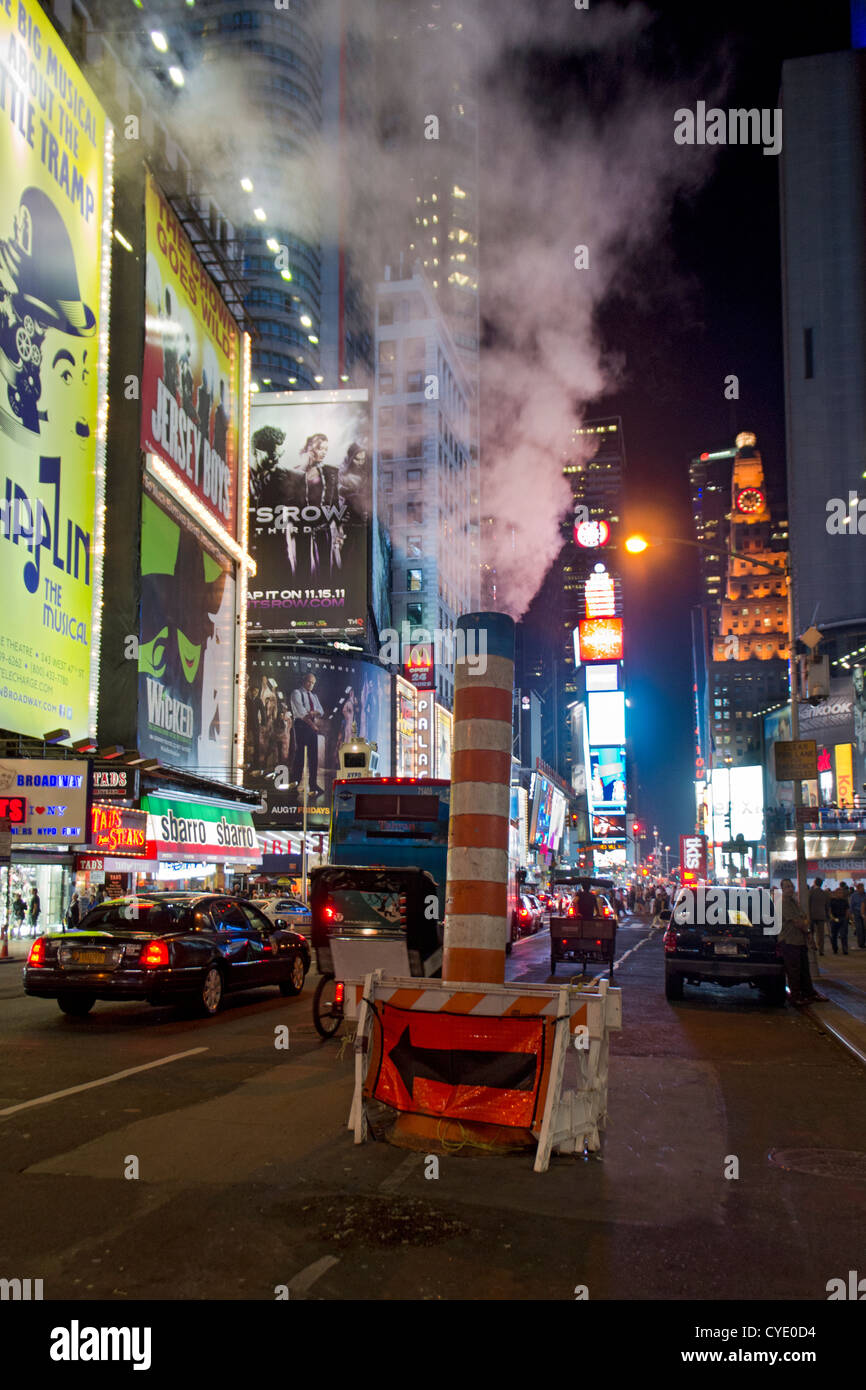 Steam rising in pipe from underground on Broadway,Times Square,New York,USA - Stock Image