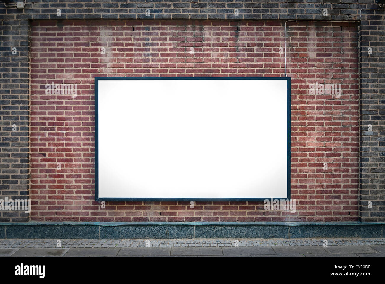 one blank billboard attached to a buildings exterior brick wall. - Stock Image