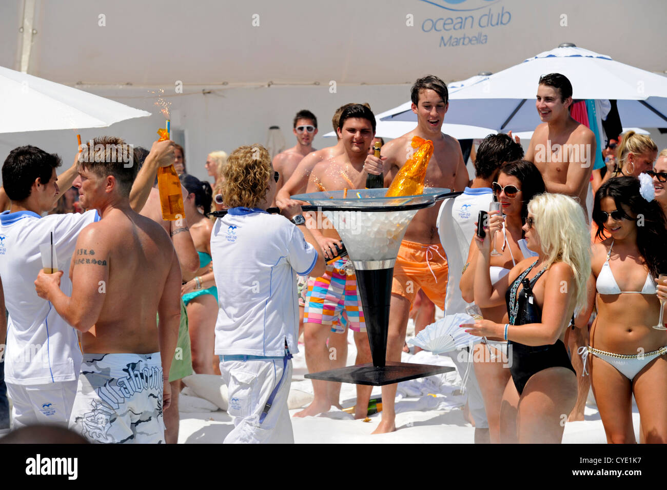 Waiters carrying a Methuselah bottle of Crystal champagne in a large ice buckets to clients at pool party . - Stock Image