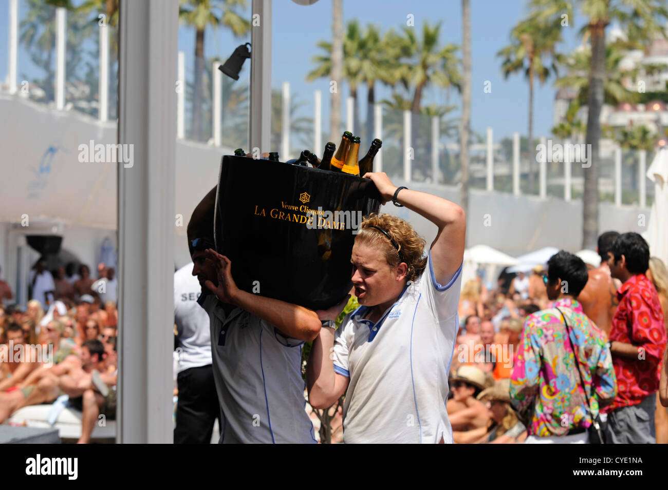 2 waiters carrying large ice bucket of empty champagne bottles after it had all been sprayed during  annual beach - Stock Image